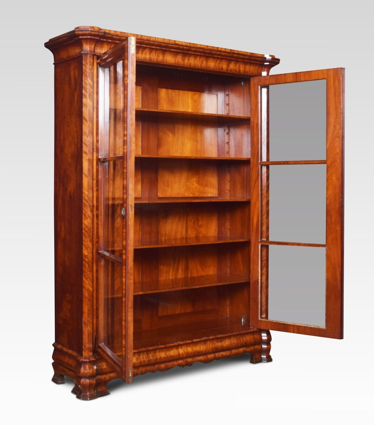 Mahogany bookcase, the moulded cornice above two glazed doors enclosing five adjustable shelves and polished flame mahogany back. To the stepped base, all raised up on bracket feet.