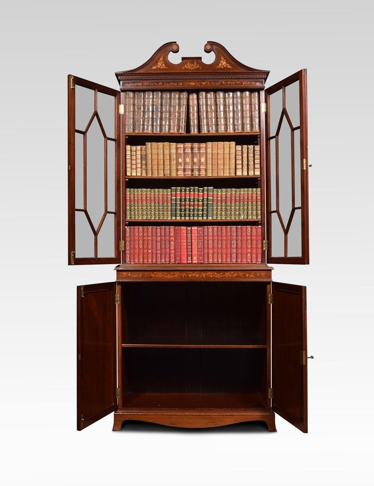 Mahogany inlaid cabinet or bookcase in the manner of Edwards & Roberts of London. The upper section with swan neck pediment and marquetry pen-work frieze. The twin astragal glazed doors open to reveal shelved interior. The solid mahogany sides with
