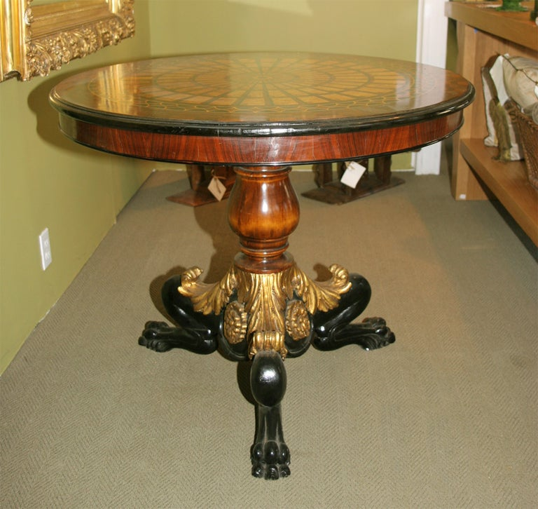 Inlaid wood parquetry design top with gilt and ebonized wood base.