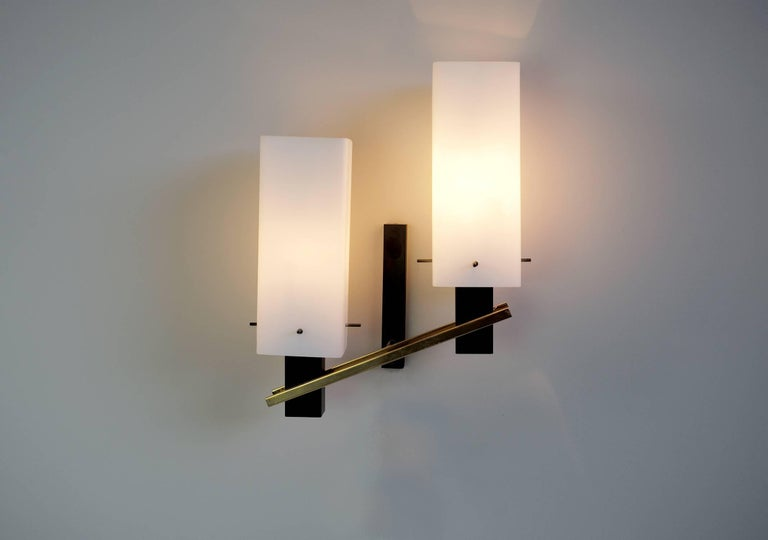 Large pair of two-light sconces in matte black metal, brass and opaline, Maison Arlus, France, 1960. Very good quality of manufacture at the service of a sober and elegant design. Perfect original condition.
