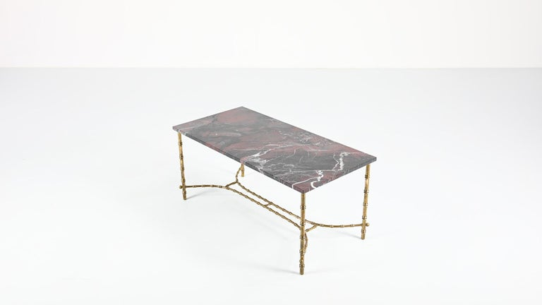 This French Neoclassical coffee table, ascribed to Maison Baguès, consist in a black and red marble top supported by a faux bambou brass structure. New marble top, excellent overall condition.