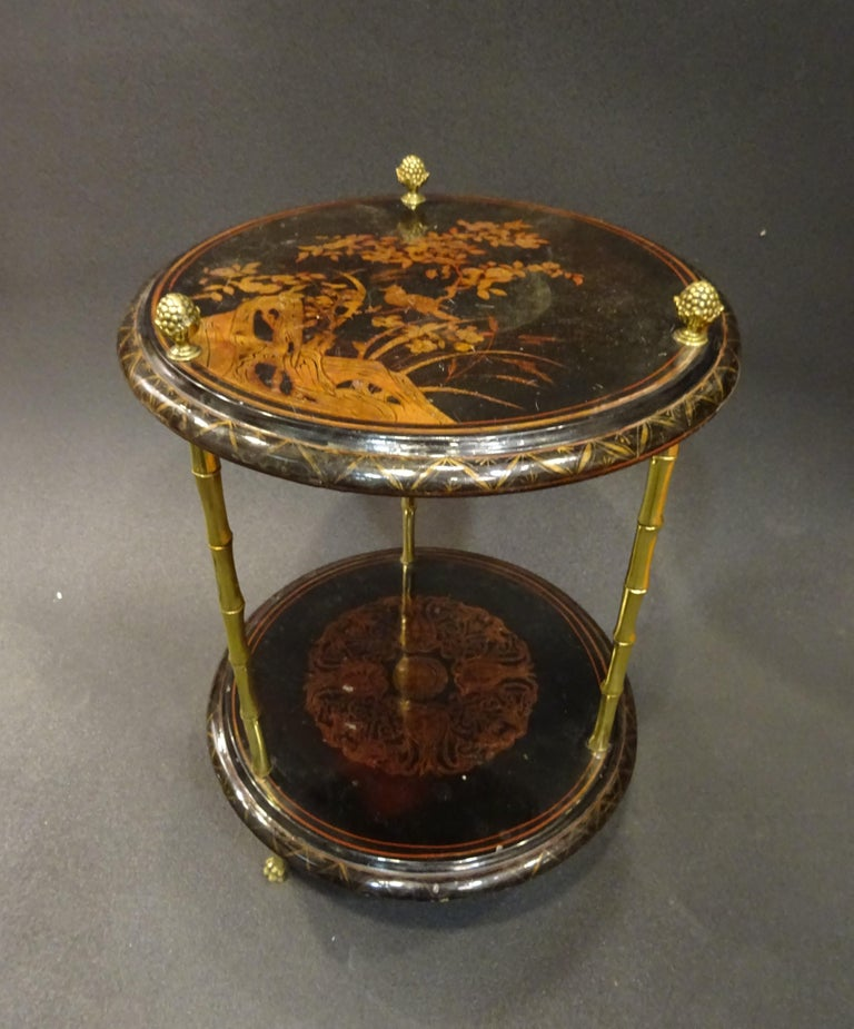 Amazing and very refined end table or gueridon by Maison Bagues, Paris, France, 1970s. 2-tier table in black lacquered good and gilt chinoiserie. Bamboo imitating legs in gilt bronce with pineapple-shaped finished. In a very good condition with age
