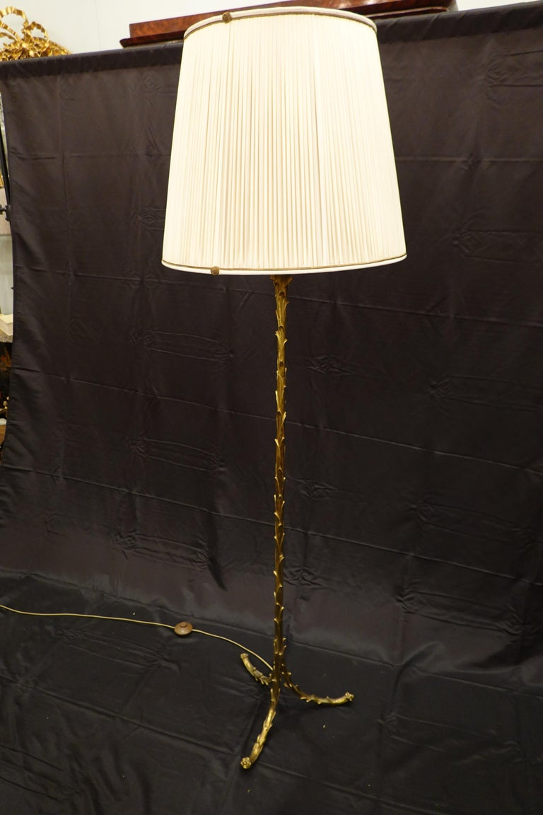 Gilt bronze floor lamp in the form of palm fronds supported on three split legs by Maison Baguès. The lamps includes a new silk, pleated lamp shade custom made in France with