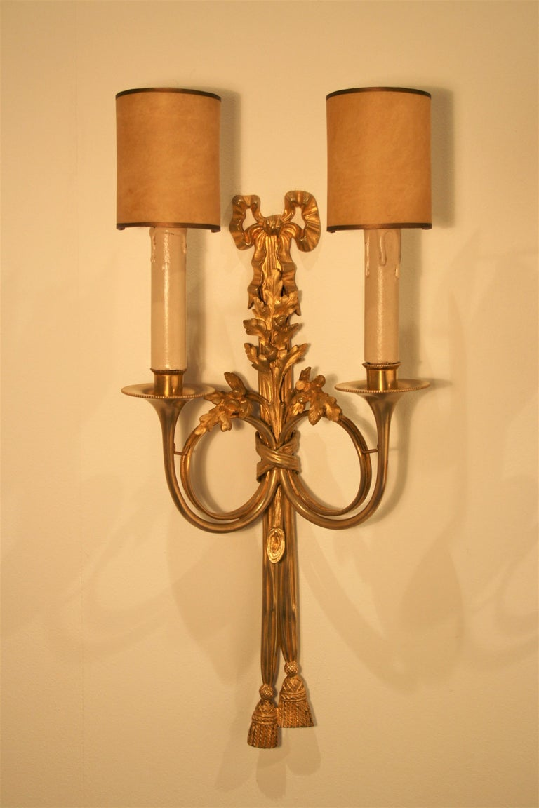 A pair of 24-carat gilt bronze sconces from the famous Maison Baguès in Paris, Louis XVI style. The electricity has been fully checked by our team and is suitable for the US. The bronze is very finely carved and the gilding that used Baguès for