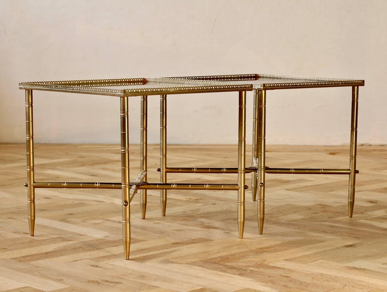 A delightful pair of vintage French midcentury side tables in the style of Maison Baguès, circa 1970s. Featuring perforated metal banding around the tabletop and 'lathed' style details on the legs and cross sections. The table tops are simply
