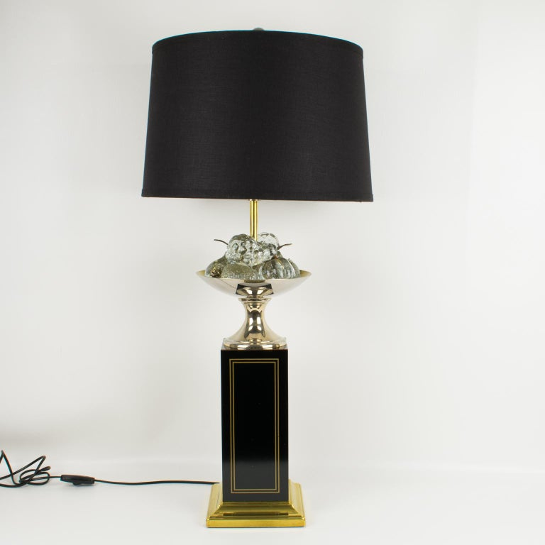 Stunning decorative tall table lamp by Maison Charles, Paris. The brass lamp is raised on a large square black enameled column with brass inlaid details. The base is brass with a stepped design. The lamp is topped with a brass bowl holding crystal