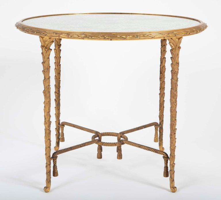 A Maison Charles round side table with finely chased bronze base with tassels and a X stretcher base having a round mirrored top.