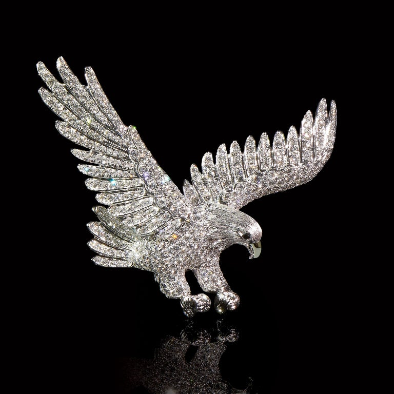 Dive    2 Sapphires (0.026ct), 353 Diamonds (3.11cts), 18K White Gold. Length: 55mm  An eagle with strong wings and legs diving down from mid-air, aims at its prey. Movement of the bird is captured in diamond and white gold.