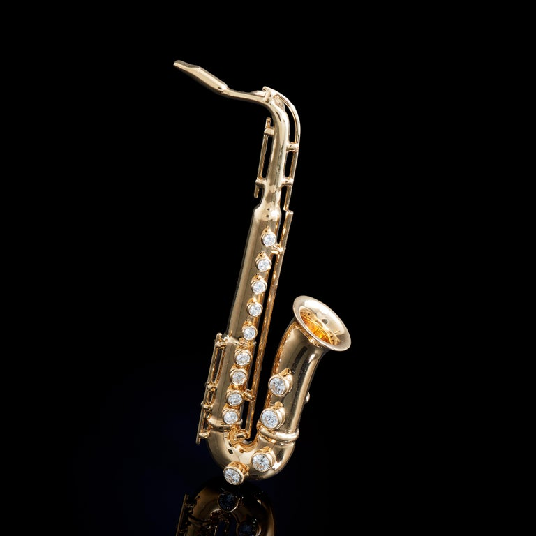 Saxophone    13 Diamonds (0.61ct), 18K Yellow Gold. Length: 60mm  This tiny musical instrument is constructed of diamonds and gold. Shapes of all musical instruments are always elegant, stream lined and beautiful, including this miniature one.