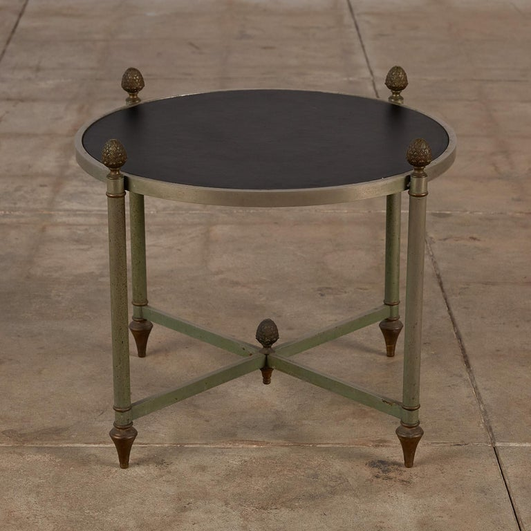 """Stainless steel and patinated bronze side table with leather top by Maison Jansen, France, c.1955. The table is raised on four tapered legs with a cruciform stretcher featuring acorn shaped finials.  Dimensions: 22.5"""" diameter x 18.25"""""""