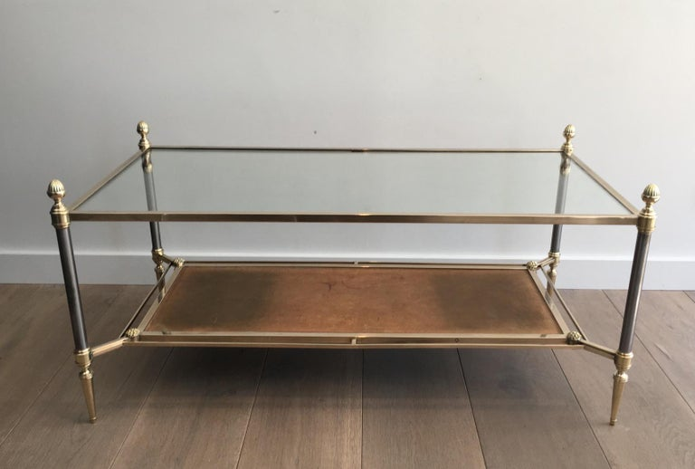 This very nice neoclassical coffee table is made of brass, with brushed steel feet, glass shelf on top and a used brown leather shelf on the bottom. This is an iconic cocktail table by the famous French maker Maison Jansen but this kind of brown