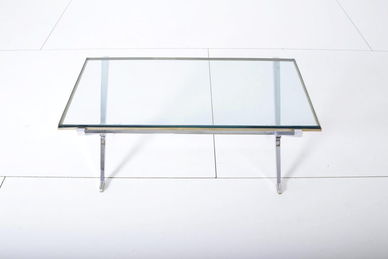 Maison Jansen chrome and brass X base coffee table. Chrome frame with glass top and brass details.