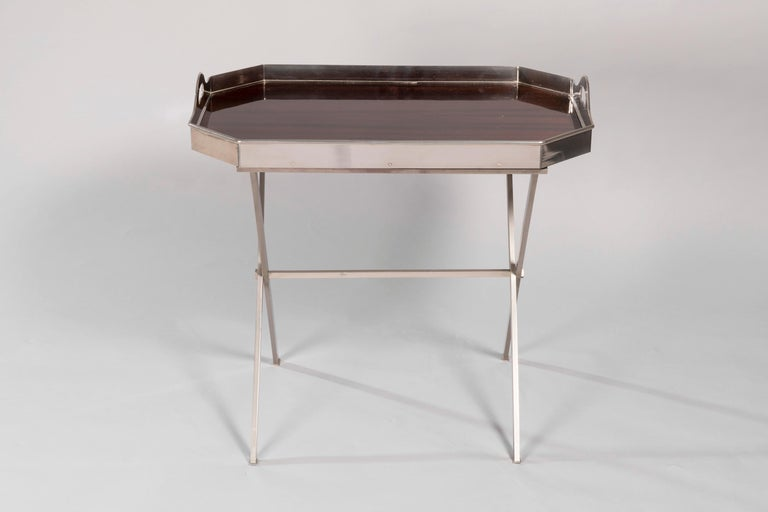 An elegant folding bar table with a removable mahogany tray and plated silver. The steel base give a modern touch to the Classic design of the tray.