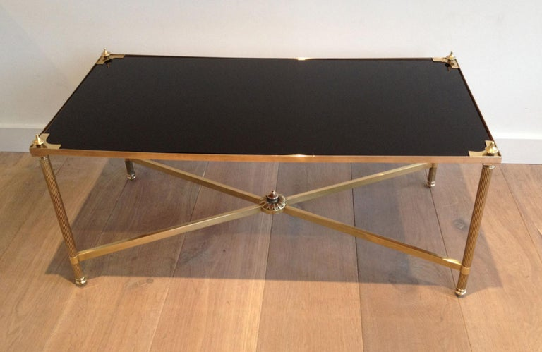 This nice neoclassical style rectangular coffee table is made of brass with fluted legs and a stretcher on the bottom part. It has a black lacquered glass shelf on top with brass triangle and finials on each corner. This is a very elegant cocktail