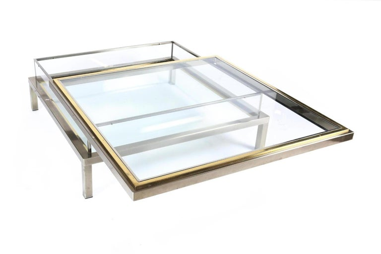 1970s coffee table in good condition. Satined chrome and brass with glass tops  The top can slide open to reveal the inside compartment that can be used as a vitrine for books and magazine.