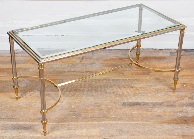 "Maison Jansen style modern brass and chrome coffee table, with curved stretcher and glass top. Measures: 18.5"" H x 38.5"" W x 18.25"" D."