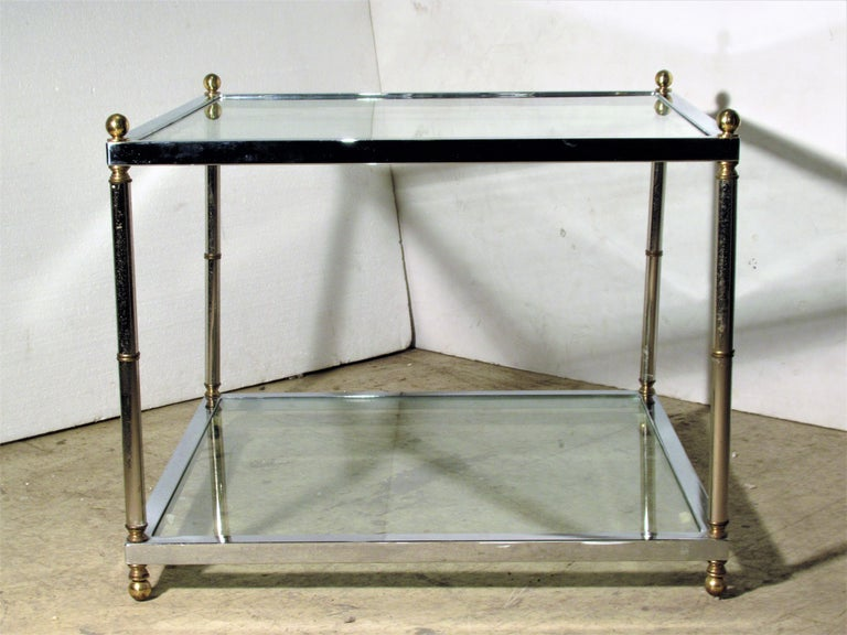 A good quality square two tier (glass top / lower glass shelf) chromed steel cocktail / coffee table with brass ball finials, brass ball feet and brass banding. In the style of Maison Jansen, circa 1970.