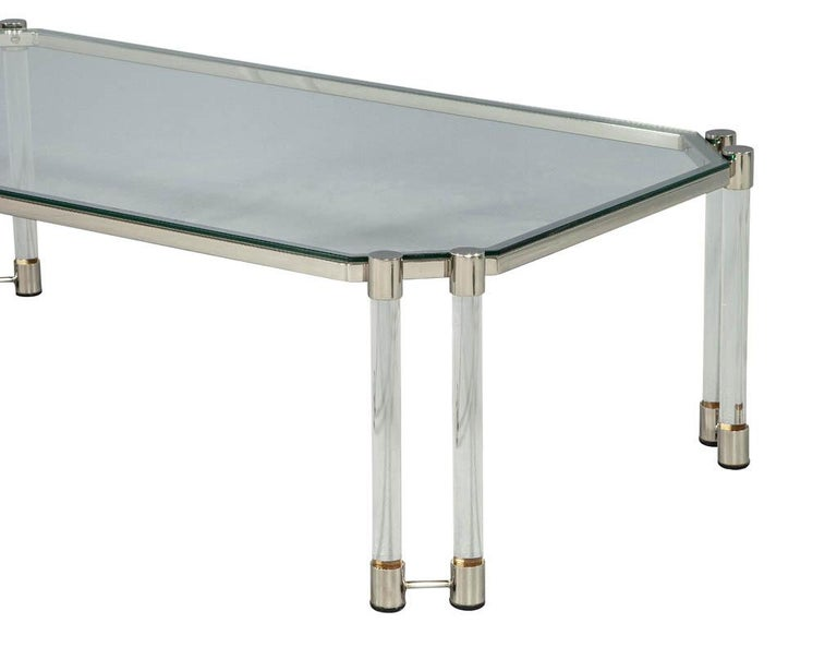 In the style of Maison Jansen, this excellent modern style cocktail coffee table features a combination of clear glass, stainless steel accents and acrylic tubular legs. Imported from Paris, France and restored by the Carrocel professionals. Please