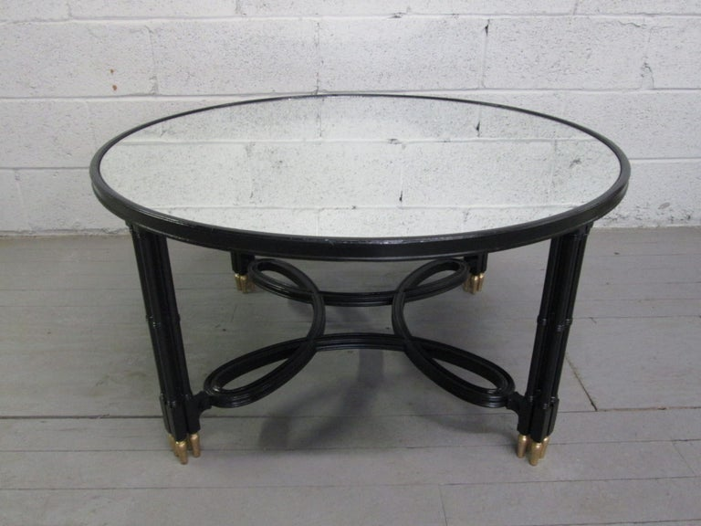 Maison Jansen style coffee table with a mirrored top. Black legs and a decorative scrolled stretcher with gold feet.