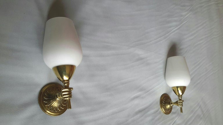 Charming original pair of neoclassical bronze sconces with white opaline lampshades tulips and figuring small hands torchere holding it in the style of the French Maison Jansen, France, circa 1950. In a very good condition, rewired to fit the US