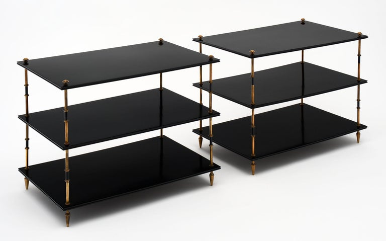 Pair of three-tiered side tables by Maison Jansen. This pair has been ebonized and finished with a lustrous French polish. The shelves are separated by solid brass and lacquered steel sections and are supported on gilt brass toupee feet.