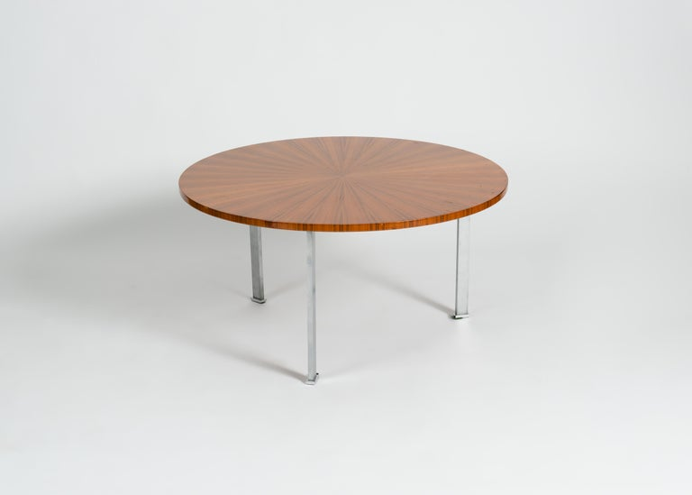 This beautiful Maison Leleu coffee table is a fine example of the firm's 1960s output -- a sleek tripodal base of aluminum topped with a perfectly circular piece of mahogany, the grain of which radiates out from its center like the rays of the