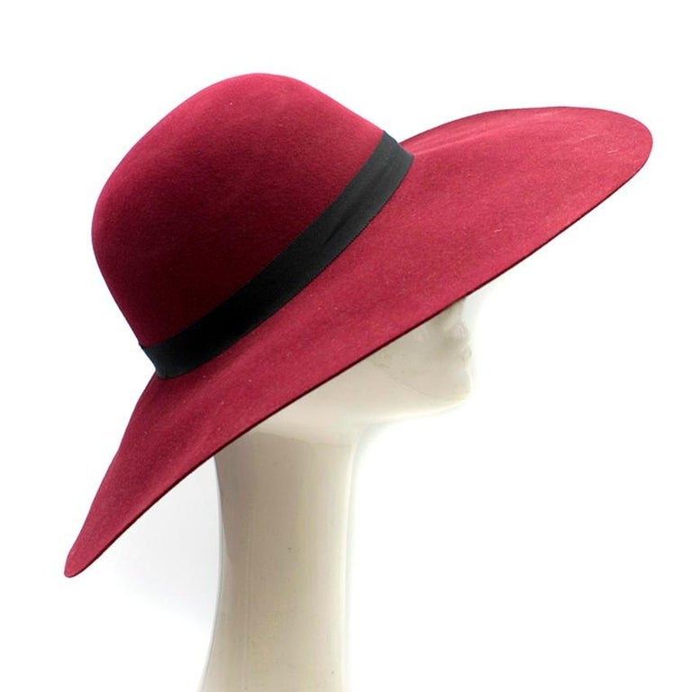 Maison Michel Burgandy Felt Wide Brimmed Hat  - Burgandy felt - Wide brimmed hat - Black ribbon wrapped around the circumference of the hat embellished with a black metal 'M'  Please note, these items are pre-owned and may show some signs of