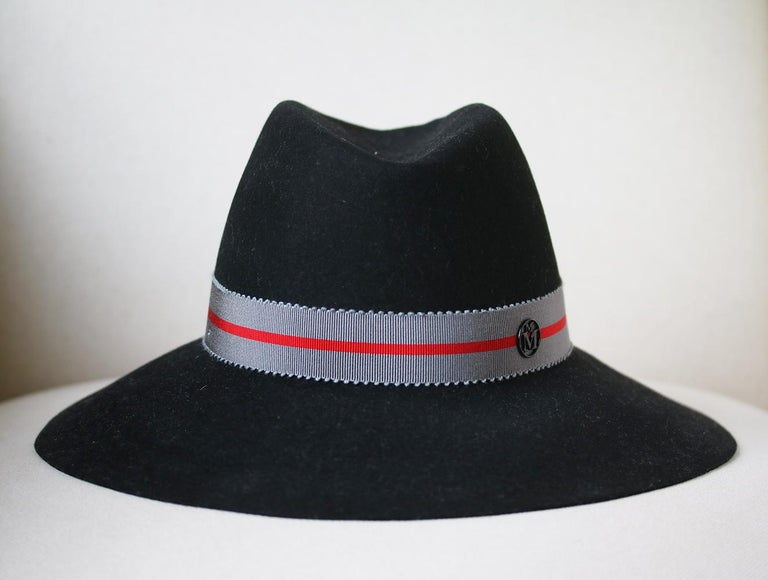 This Maison Michel hat is rendered in rabbit felt and features a two tone band. Two tone band. Wide brim. Composition: Rabbit felt. Colour: black. Slip on. Made in France.  Size: Medium (Circumference - 56 cm, Brim depth - 8 cm)  Condition: As new