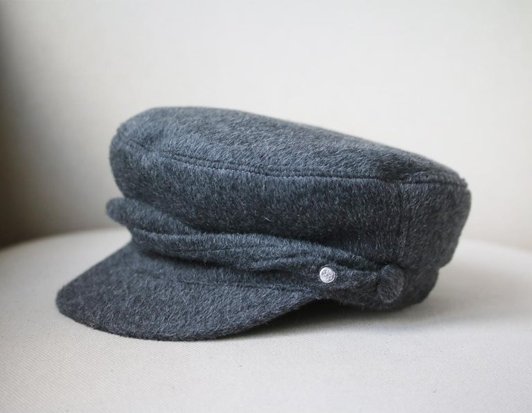 This Maison Michel hat is rendered in angora and wool blend. It features an edgy design and is accented with an embelishment band. Baker Boy Hat Silhouette. Unlined. 70% Angora, 30% Wool. Colour: Grey. Made in France.   Size: Medium (Circumference -