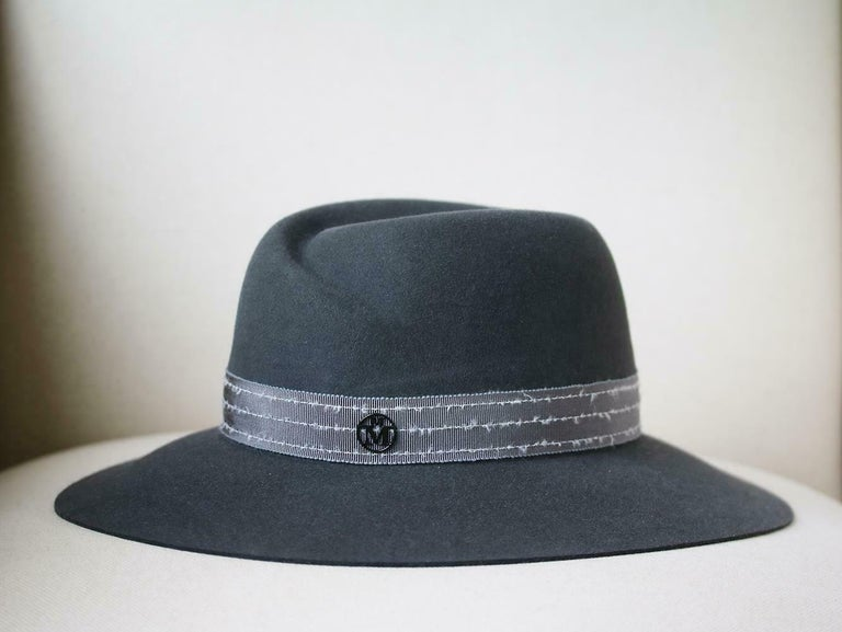 Virginie is a fedora hat. It is presentend here in dark grey waterproof rabbit furfelt. It is embellished by a dark grey grosgrain ribbon with white frayed overstitches. 100% Rabbit felt.   Size: Large (Circumference - 60 cm, Brim depth - 8