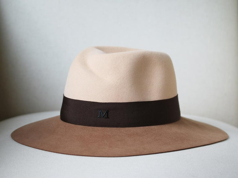 Couture millinery, Maison Michel, is renowned for its expert craftsmanship. This two-tone rabbit-felt fedora is impeccably constructed by hand and fitted with an elasticated internal brow band. The chocolate grosgrain trim is adorned with a metal