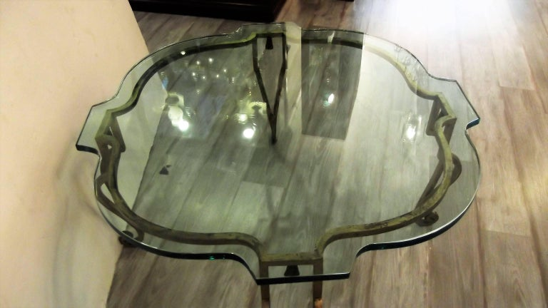 Elegant French glass and distressed gilt iron cocktail table attributed to Maison Ramsey. The custom scalloped top resting on a hand forged shapely iron base with a worn gilt finished surface. Nice medium size with open and airy feel. There are
