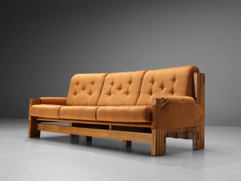 Maison Regain, sofa, elm, fabric, France, 1960s  This sofa was designed by Maison Regain in the 1960s. The three seater has comfortable backseat thanks to the structured, yet soft looking cushions. The fabric is extended on the armrests of the
