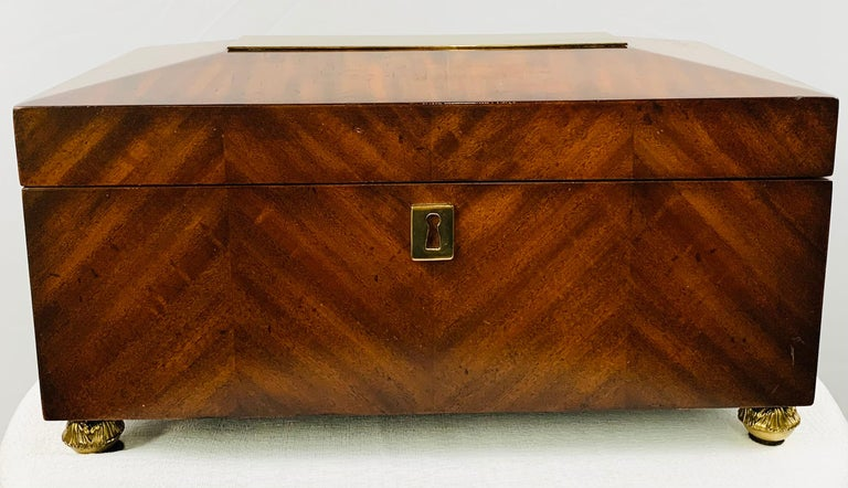An elegant 1970s large mahogany wood box signed Maitland Smith. The box features fine brass rectangular design on the top and gilded round feet. This timeless box will decorate your room and is large enough to store many items such as cigars,