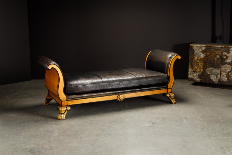 A beautiful Maitland Smith Clawfoot daybed in the Empire Revival style featuring gilt and ebonized claw feet, gilt lion medallions, studded scroll arms, and a big plush comfortable cushion. The light colored wood has a smooth lacquered finish with