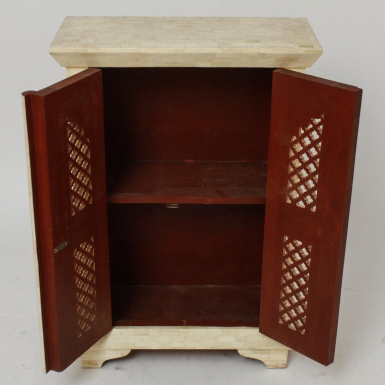 Modern Maitland Smith style tessellated side table cabinet with shaped top and two doors. The piece is featuring stylized arches and a decorative lattice motif. In great vintage condition with age-appropriate wear and use.