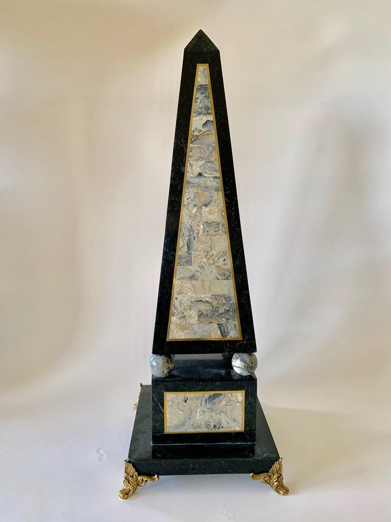 Decorative Maitland Smith tessellated black marble obelisk circa the 1980s, comprised of a mixture of tessellated colored marble. The decorative center features hues of greys which are outlined in gold emphasizing the architectural geometric pattern