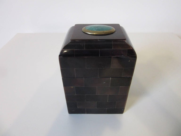 A decorative box with tessellated horn in dark brown tones and a blue green gem stone to the lid surrounded by a brass bezel. When opened the inside revels a caramel colored Philippine mahogany interior, retains the manufactures label to the bottom