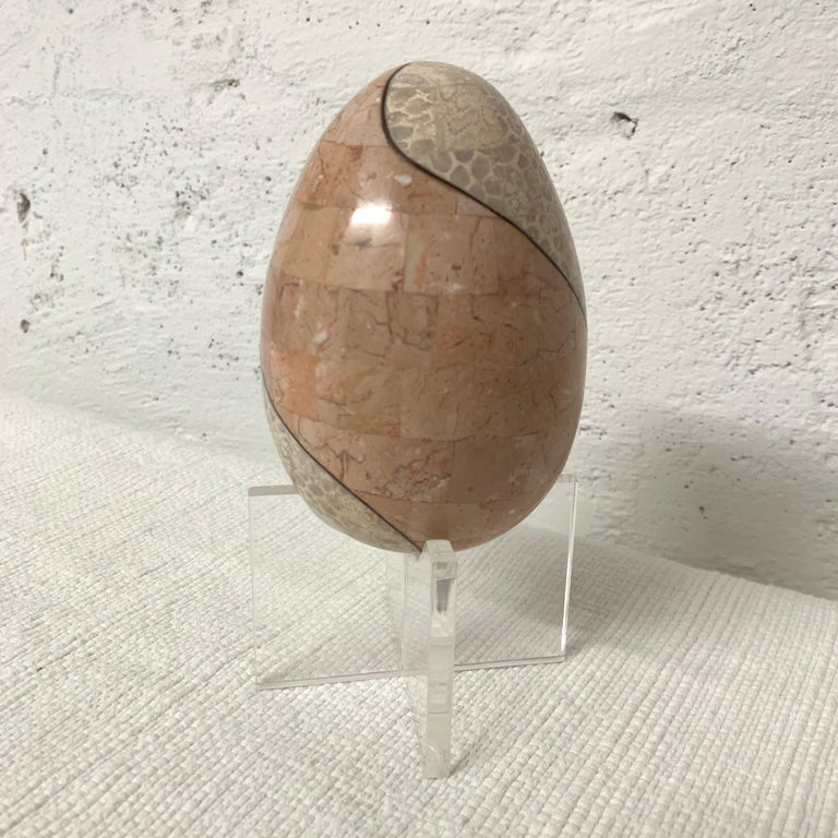 Unique egg on a Lucite stand rendered in bicolored tessellated marble with a bronze inlay by Maitland Smith.