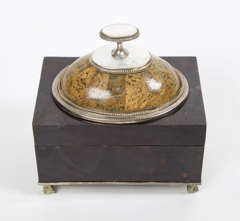 Maitland Smith tessellated stone box with a mother of pearl finial handle. The interior of the box is lined with a black felt and has a removable lid. The box rests on sterling silver ball and claw feet as well as the entirety of the box is framed