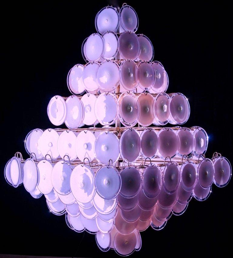 A chandelier of rare beauty and elegance. 136 Murano glass discs amethyst by Gino Vistosi, disposed in ten rows, forming two overlapping pyramids. A pair is available.  DIMENSIONS H 55.12 in.  without chain x W 39.38 in. x D 39.38 in. H 140 cm
