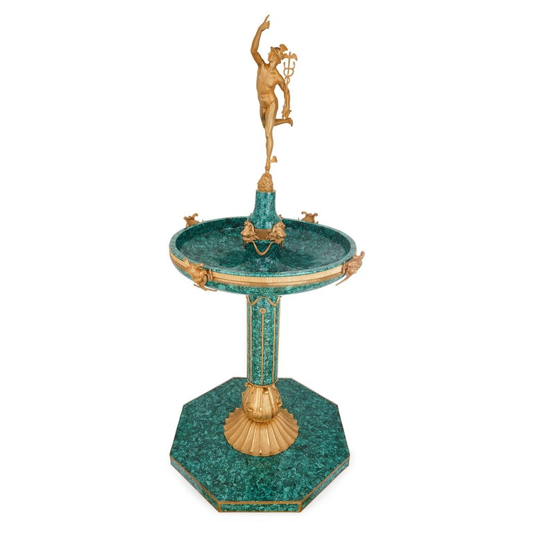 This Italian fountain showcases extremely skilled design and craftsmanship, with Classical detailing all-over. It dates to the late 19th century, with later malachite veneer. The fountain is mounted at the top with a gilt bronze statue of the Roman