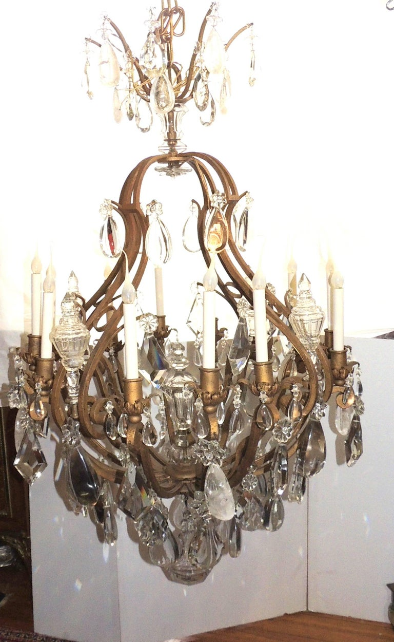 This wonderful very large 1920s gilt iron French cage chandelier has twelve lights with an assortment of flat, prism, faceted and rock crystals finished with a large beveled ball at the bottom. In the Baguès manner  Measures: 55