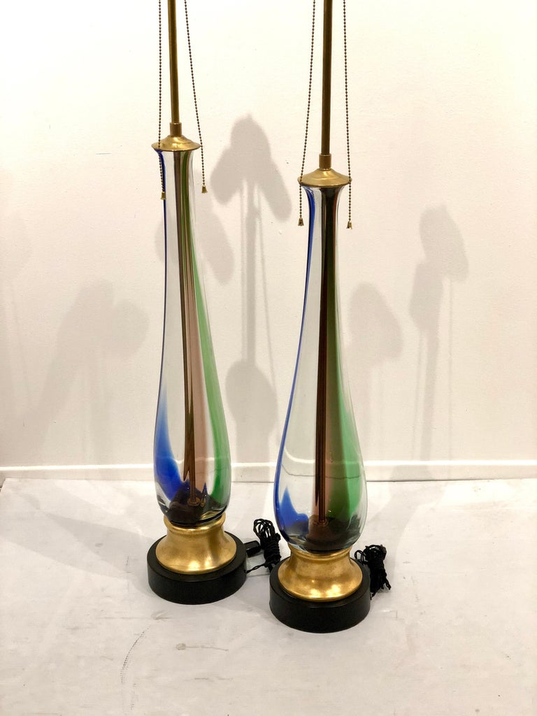 Beautiful impressive pair of table lamps by Murano, Venini freshly rewired gold leaf base double socket that adjust to desirable height, new cloth cord excellent condition lampshades not included. Beautiful colors.