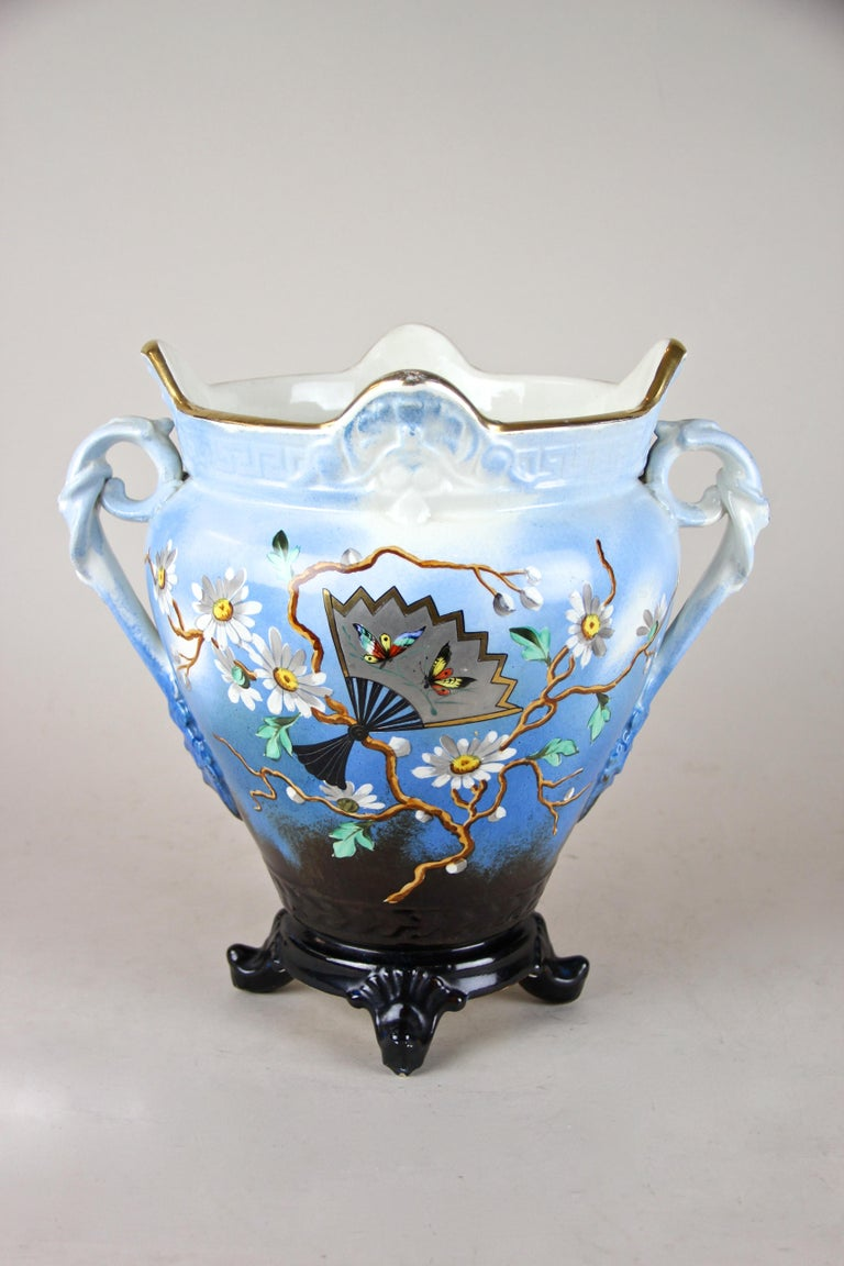 Decorative Majolica Cachepot from the late Art Nouveau/ early Art Deco period in France, circa 1915. The great shaped light blue colored body impresses with its beautiful floral design showing awesome hand painted marguerites. The front is