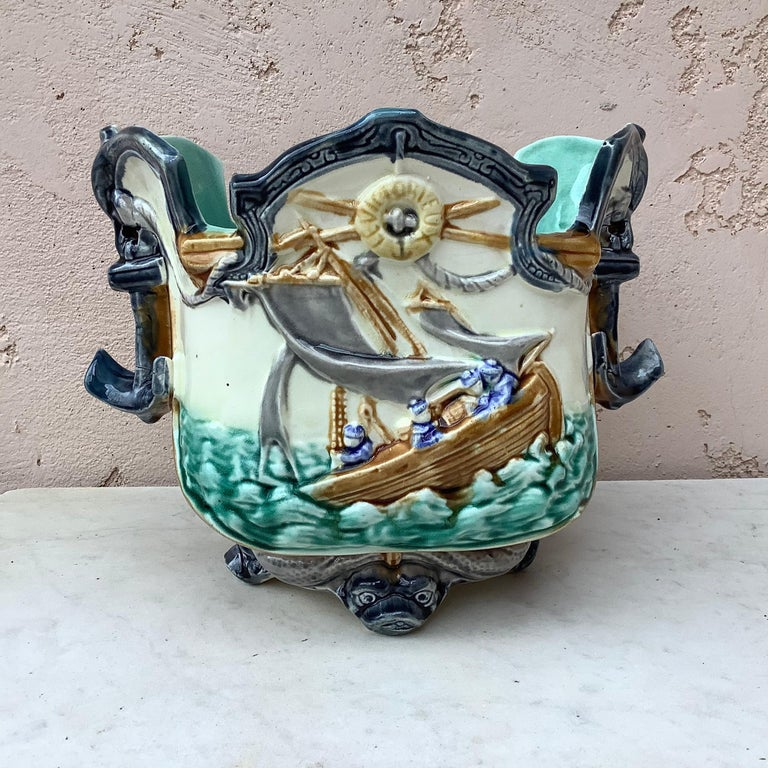 19th century Majolica nautical planter cachepot signed Onnaing, the feets are dolphins and the front is decorated with boats on the sea, the handles are anchors.