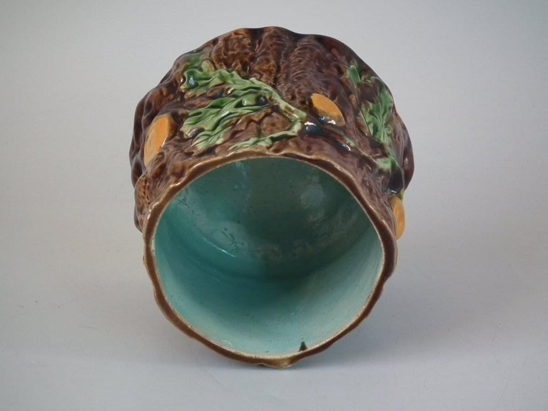 Majolica pot and cover which features oak leaves and acorns on a bark ground. Coloration: brown, green, ochre, are predominant.