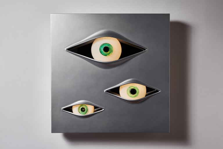 Malizia wall light by Angelo Brotto. Originally designed in 1973. Current production manufactured in Italy by Esperia. Luminous wall sculpture made with a panel of brushed aluminum and three eyes made of Murano glass. Takes three 11w LED bulbs.