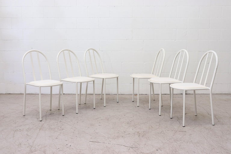 Mod Mallet Stevens and Thonet style white enameled metal stacking chairs with white vinyl seat cushion. In original condition with visible wear. Some of the seating may have small tears. Wear is consistent with their age and use.