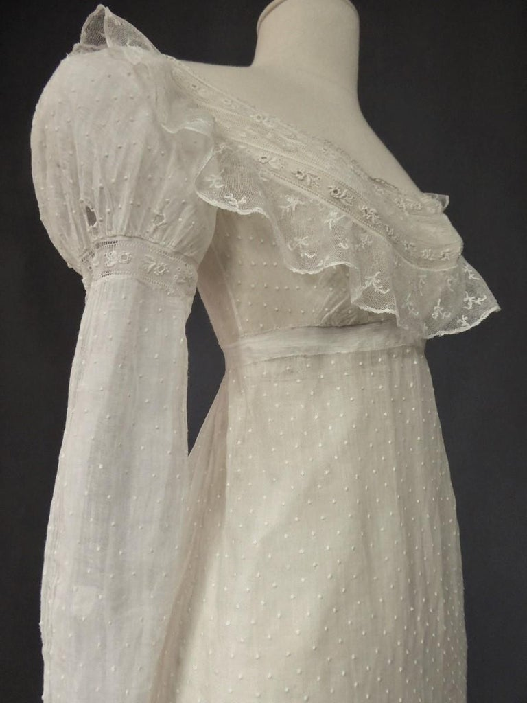 Circa 1810 France  Day dress in muslin and veil embroidered with plumetis, Mameluck sleeves , dating from the first French Empire. Large neckline in lace on a high-waisted fitted bodice. Small balloon sleeves with eyelets for tightening with a